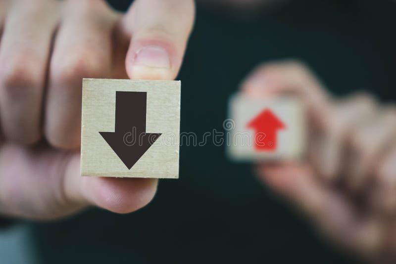 Deux cubes en bois dans les mains d'un homme de croissance et développement rouge et noire, rouge de moyens, et de moyens noirs d photographie stock