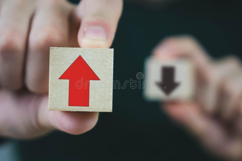 Deux cubes en bois dans les mains d'un homme de croissance et développement rouge et noire, rouge de moyens, et de moyens noirs d image libre de droits