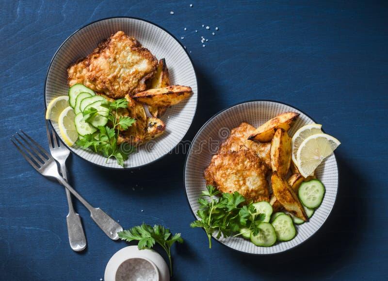 Deux cuvettes avec les poissons frits et l'ail ont fait des pommes de terre cuire au four sur un fond bleu, vue supérieure Casse- images libres de droits