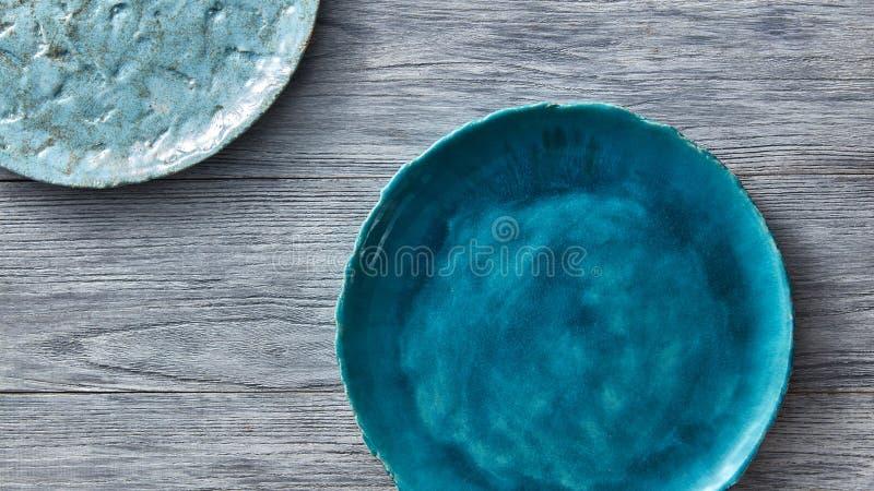 Deux cuvettes bleues de porcelaine sur une table en bois grise Plats faits main de vintage en céramique multicolore Vue supérieur photos stock