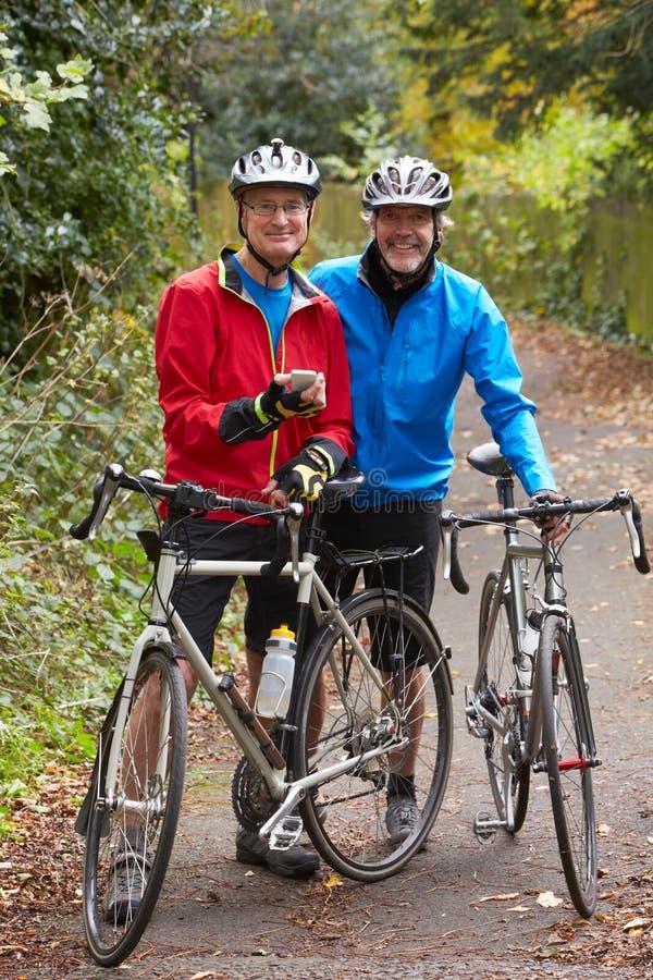Deux cyclistes masculins mûrs sur le tour regardant le téléphone portable APP image stock