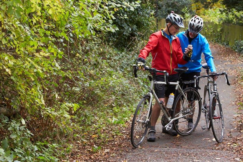 Deux cyclistes masculins mûrs sur le tour regardant le téléphone portable APP images libres de droits