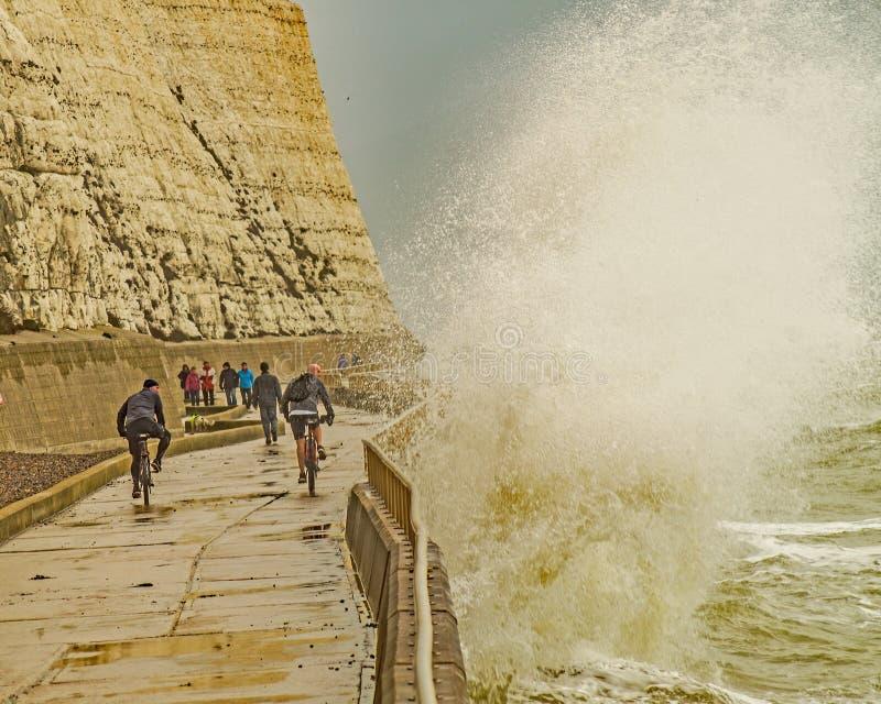 Deux cyclistes sur Brighton Seafront pris par surprise par une vague énorme images libres de droits