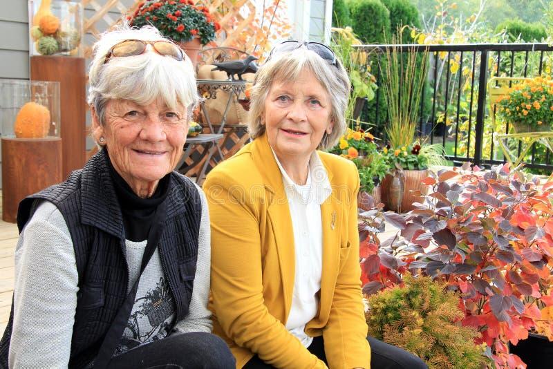 Deux dames supérieures assises sur un patio images stock