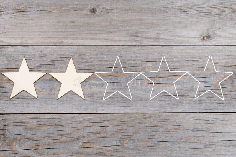 Deux de cinq étoiles dans une rangée sur les planches en bois, concept de évaluation photos stock