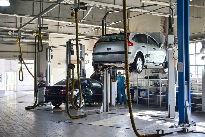 Deux des voitures d'occasion avec un capot ouvert augmenté sur un ascenseur pour réparer le châssis et le moteur dans un atelier  photo stock