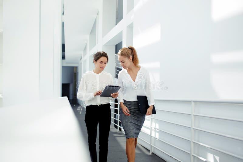 Deux directeurs généraux féminins discutant des idées du projet sur le comprimé numérique tout en marchant vers le bas dans le ha images libres de droits