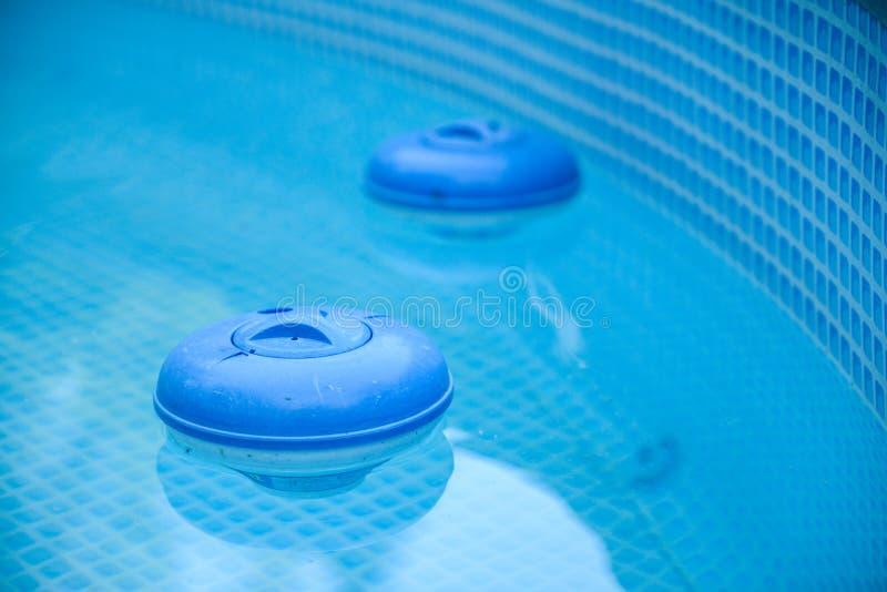 Deux distributeurs bleus de chlore se reposant dans la piscine photographie stock