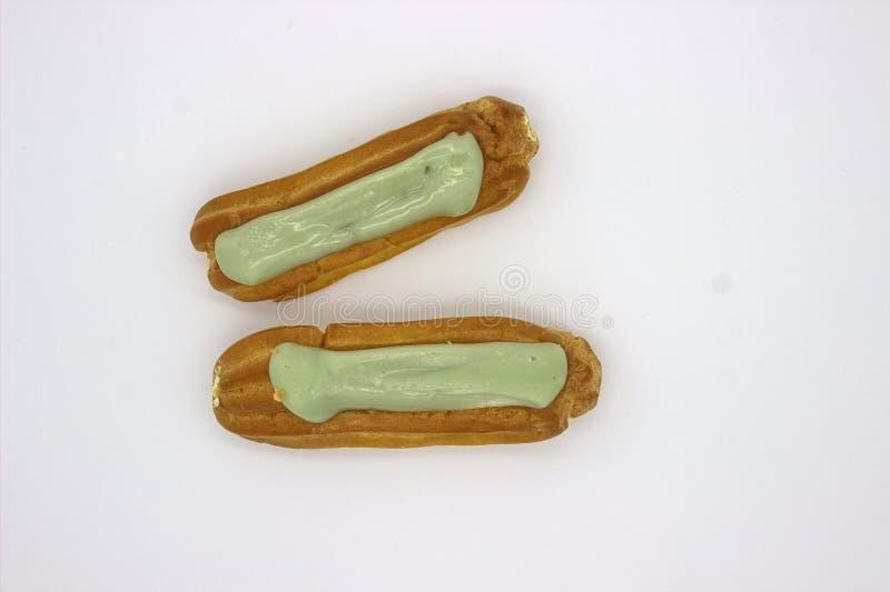 Deux Eclairs d?licieux de pistache Une image d'isolement sur le fond blanc photos stock