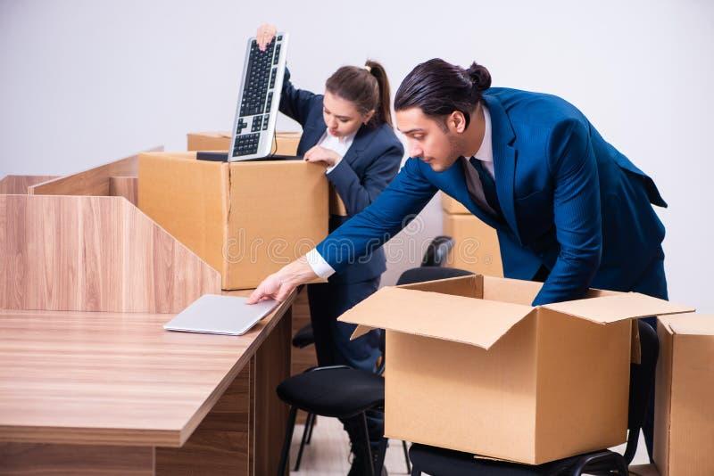 Deux employés étant mis le feu de leur travail images stock