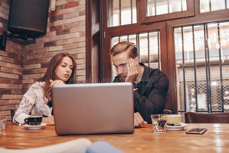 Deux employés inquiétés lisant la mauvaise nouvelle dans un ordinateur portable photographie stock libre de droits