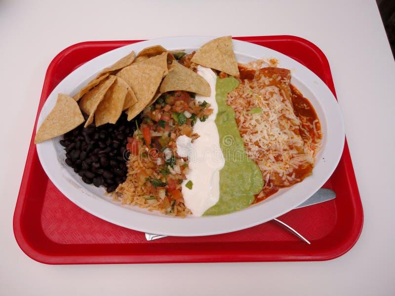 Deux enchiladas avec du riz espagnol, Pico de Gallo, puces, crème sure, guacamole, et haricots noirs photo libre de droits