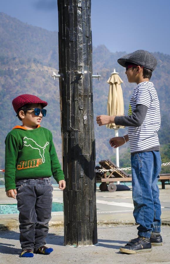 Deux enfants élégants utilisant des chapeaux ayant l'amusement ensemble photographie stock