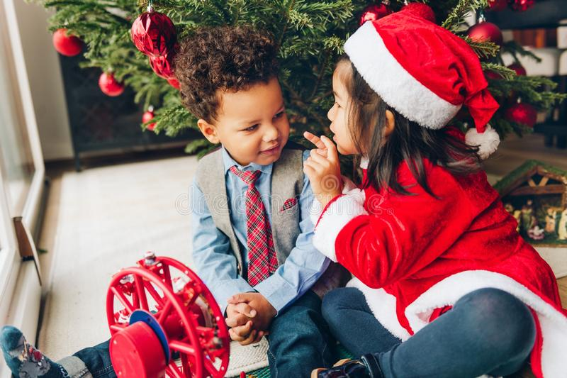 Deux enfants 3 an adorables jouant par l'arbre de Noël image libre de droits