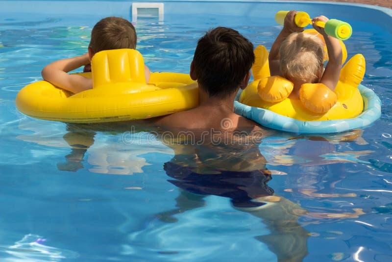 Deux enfants avec un entraîneur, avec le papa apprennent à nager dans la piscine, vue arrière soins, vacances Cercles gonflables  photos stock