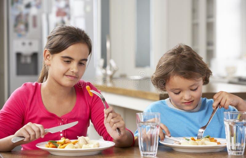 deux enfants ayant le repas dans la cuisine ensemble image stock image 55895803. Black Bedroom Furniture Sets. Home Design Ideas