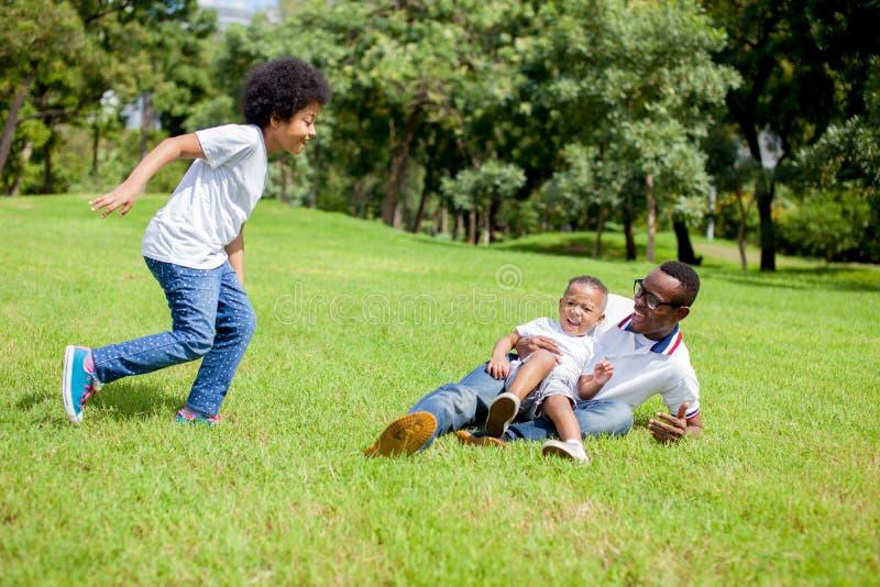Deux enfants chassant et jouant ensemble tandis que le papa attrapait un garçon dedans images libres de droits