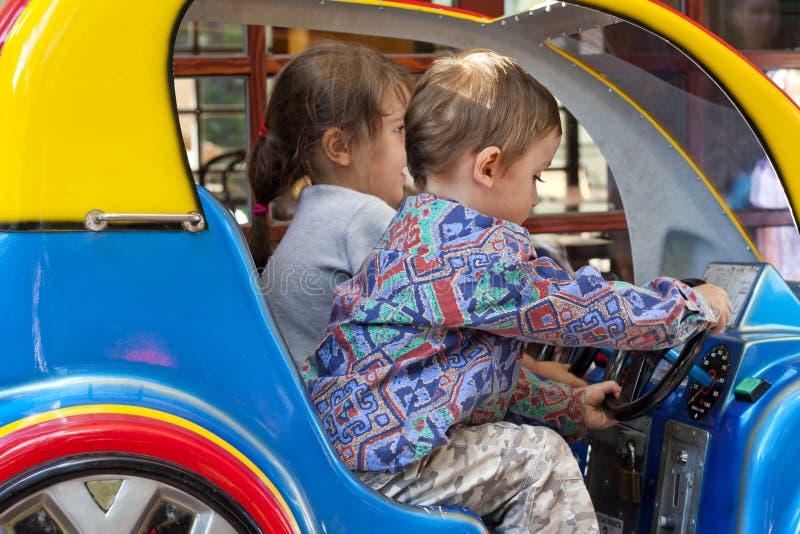 Deux enfants conduisant le véhicule de jouet images libres de droits