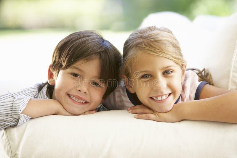Deux enfants détendant sur Sofa At Home images libres de droits