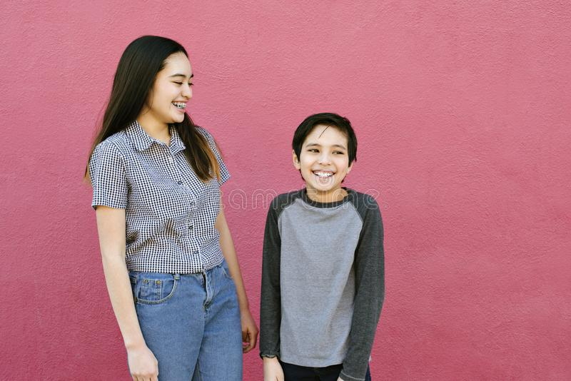 Deux enfants d'enfant de mêmes parents se tiennent contre un mur rose riant et ayant l'amusement photo libre de droits