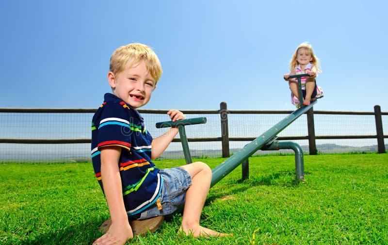 Deux enfants dans la cour de jeu photo stock