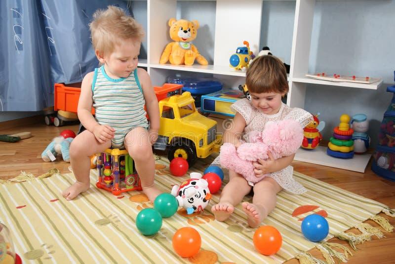 Deux enfants dans la salle de jeux avec les jouets 2 photos stock