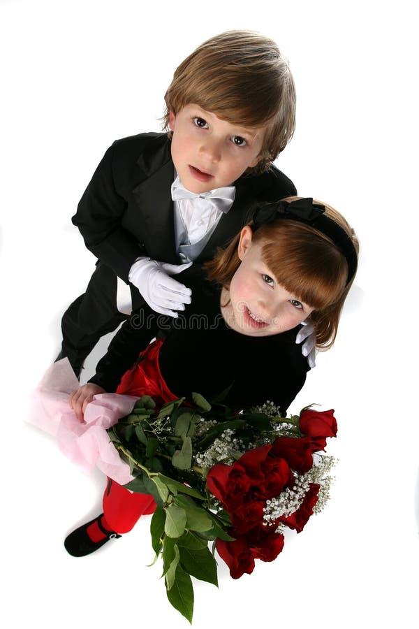 Deux enfants dans le vêtement formel et les roses rouges image libre de droits