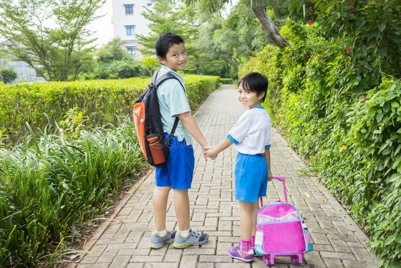 Deux enfants de mêmes parents allant à l'école ensemble images stock