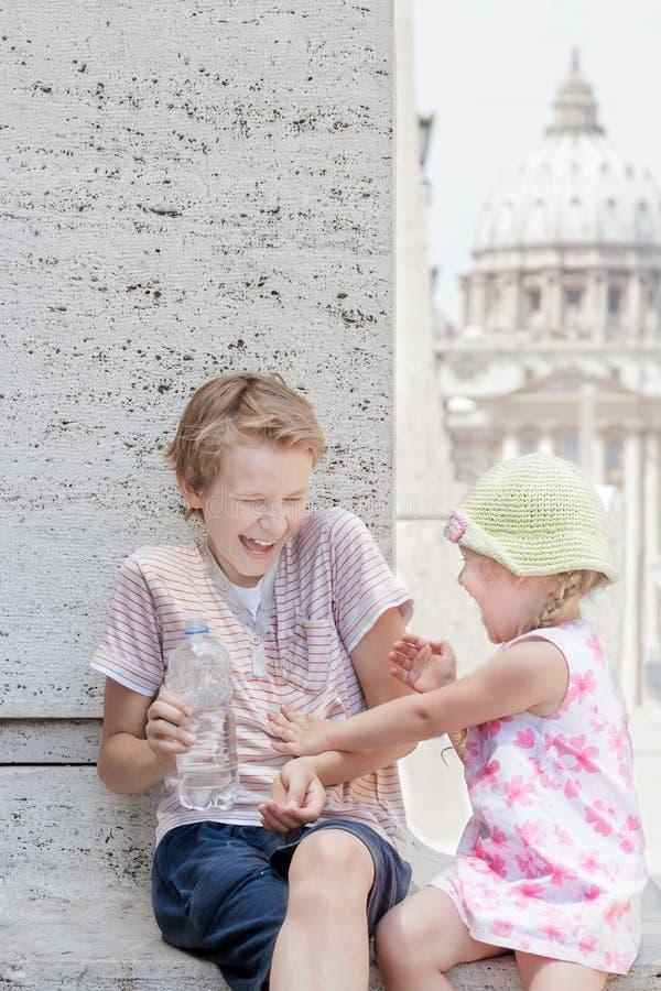 Deux enfants de mêmes parents ayant l'amusement avec de l'eau de bouteille en plastique dans le jour d'été chaud image stock