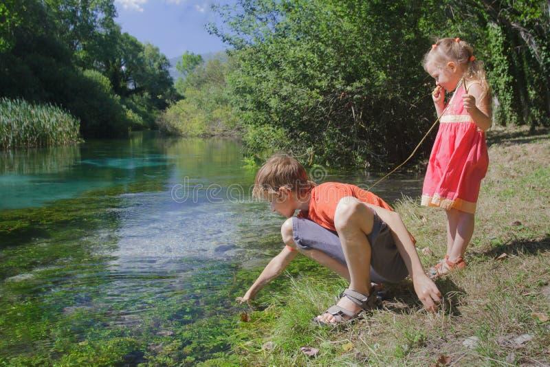 Deux enfants de mêmes parents jouant sur la berge de Tirino d'Italien avec le bâton photos libres de droits