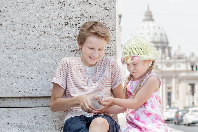 Deux enfants de mêmes parents partageant la bouteille en plastique d'eau potable dans le voyage de ville pendant le jour d'été ch photos libres de droits