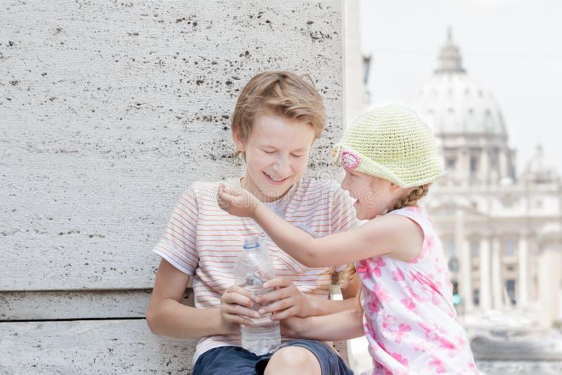 Deux enfants de mêmes parents s'imbibant eau potable de bouteille en plastique dans le jour d'été chaud photo stock