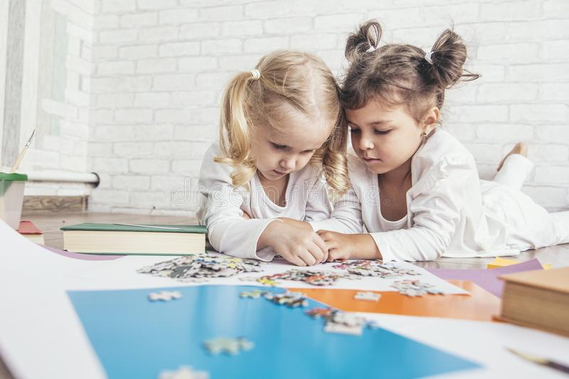 Deux enfants, de petites filles d'âge préscolaire ont mis le toget de puzzle photos libres de droits