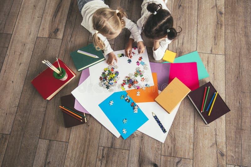 Deux enfants, de petites filles d'âge préscolaire ont mis le toget de puzzle photographie stock