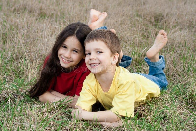 Deux enfants de sourire sur l'herbe d'automne image libre de droits