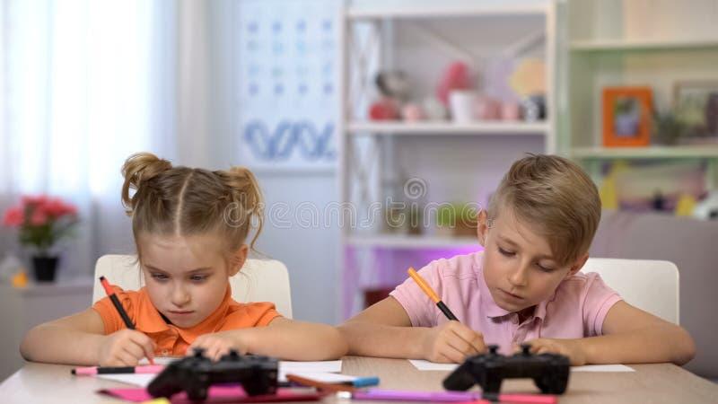 Deux enfants dessinant des images avec les stylos feutres, consoles se trouvant sur la table photographie stock libre de droits