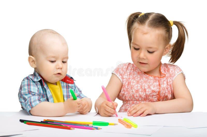 Deux enfants dessinent sur le papier utilisant des repères photos libres de droits