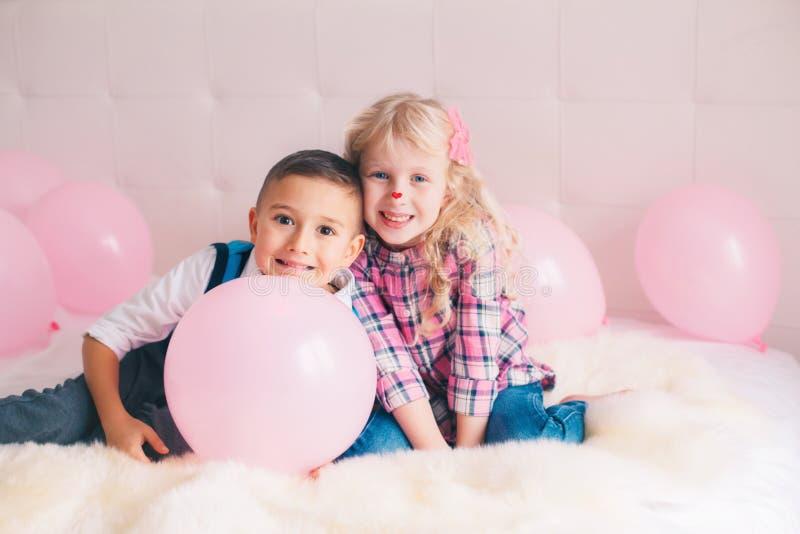 deux enfants drôles adorables mignons caucasiens blancs heureux se trouvant sur le lit images stock