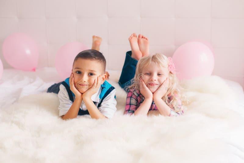 deux enfants drôles adorables mignons caucasiens blancs heureux se trouvant sur le lit photo stock