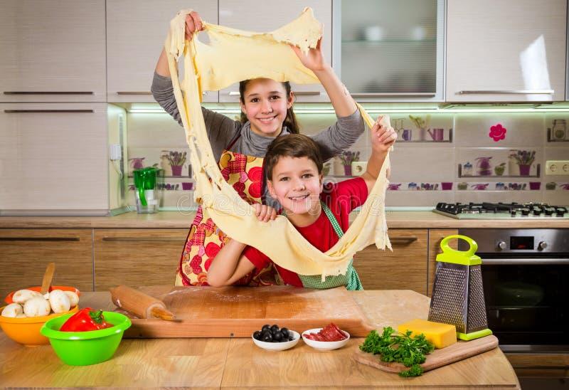 Deux enfants drôles malaxant la pâte, faisant la pizza images libres de droits
