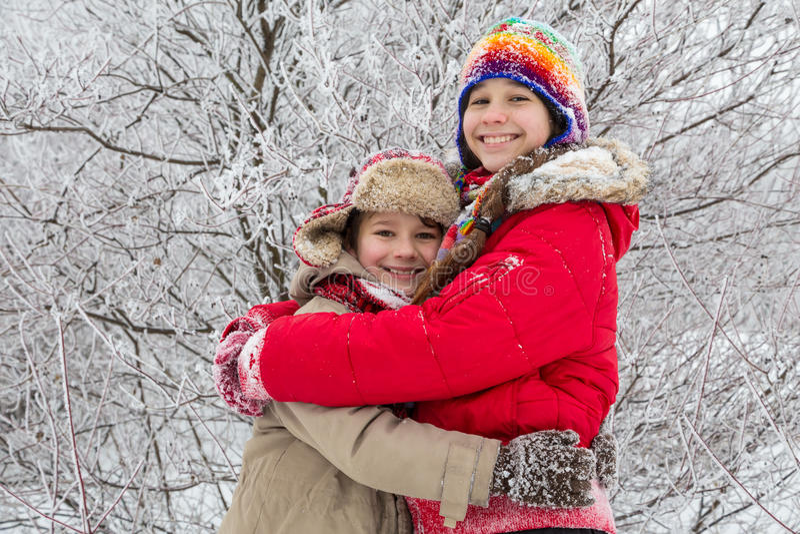 Deux enfants embrassant ensemble sur la forêt d'hiver photographie stock libre de droits