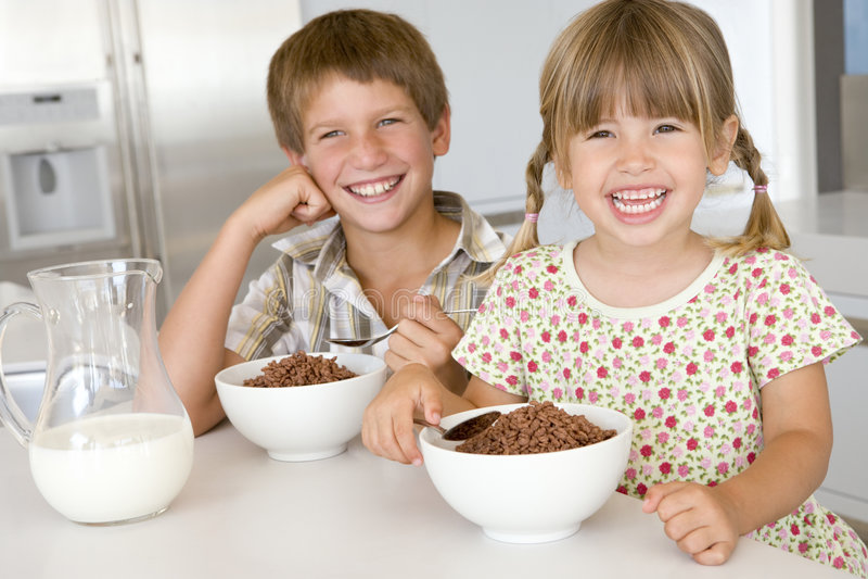 Deux enfants en bas âge dans la cuisine mangeant de la céréale photos libres de droits