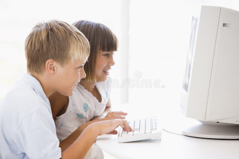 Deux enfants en bas âge dans le Home Office avec l'ordinateur photos stock