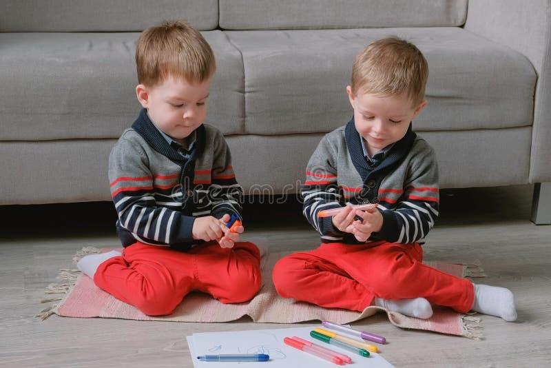 Deux enfants en bas âge de frères jumeaux réunissent des marqueurs se reposant sur le plancher images libres de droits