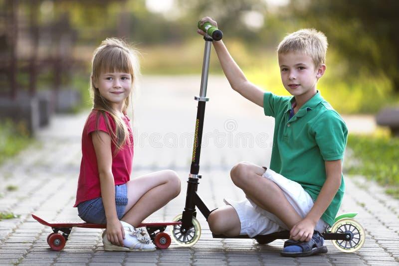 Deux enfants en bas âge de sourire drôles heureux mignons, frère et soeur, posant pour la caméra, le garçon avec le scooter et as photographie stock