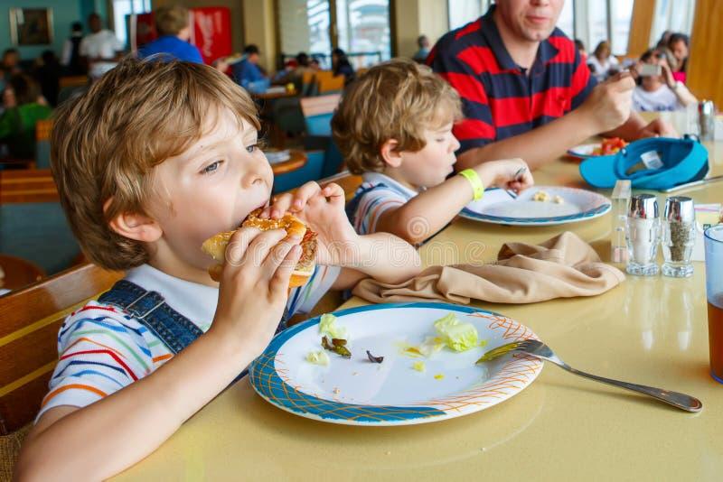 Deux enfants et garçons préscolaires de père mangeant l'hamburger de pâtes se reposant en café sur le bateau de croisière Enfants images libres de droits