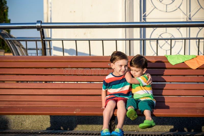 Deux enfants, frères de garçon, s'asseyant sur un banc en parc, winterti photo libre de droits