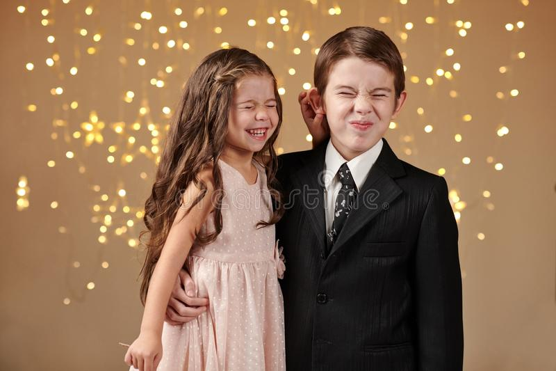 Deux enfants garçon et fille sont dans des lumières de Noël, fond jaune, concept de vacances d'hiver image stock