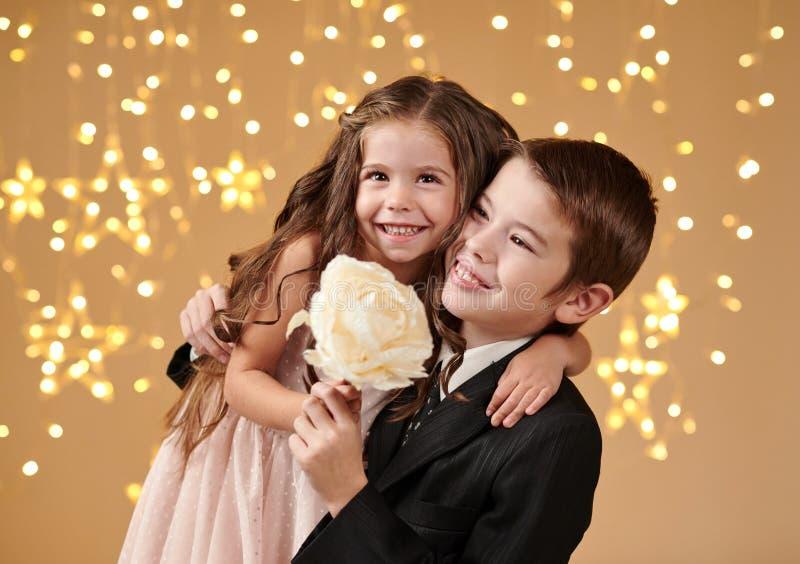 Deux enfants garçon et fille sont dans des lumières de Noël, fond jaune, concept de vacances d'hiver photographie stock libre de droits