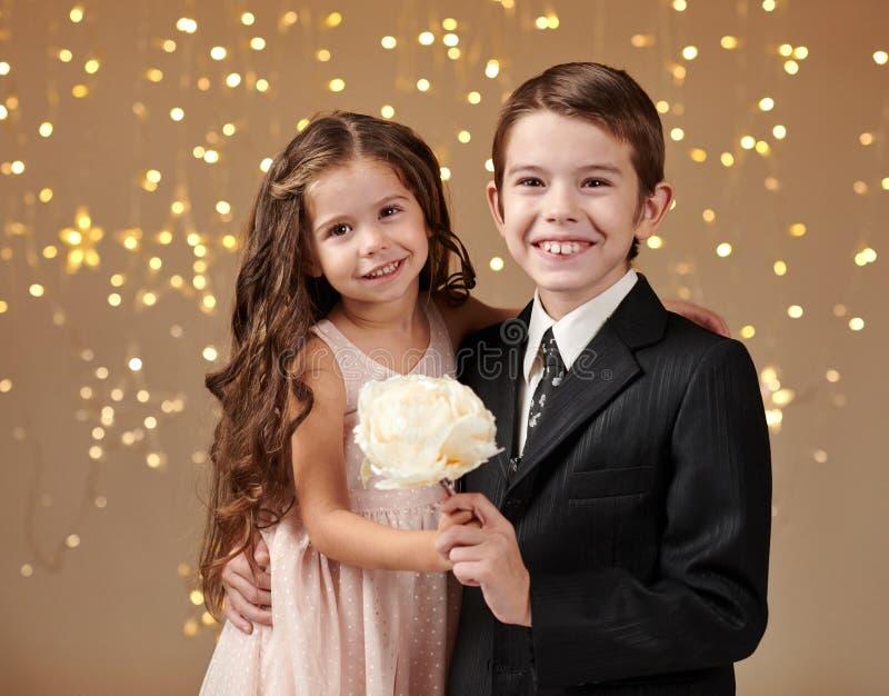 Deux enfants garçon et fille sont dans des lumières de Noël, fond jaune, concept de vacances d'hiver image libre de droits